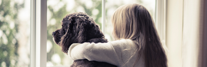 girl hugging dog looking out window