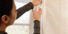 Woman draftproofing a window